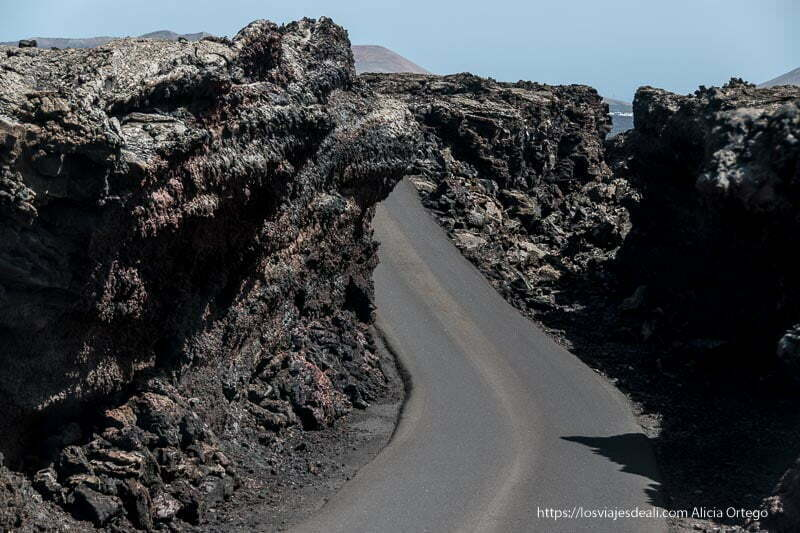 carretera con paredes de lava a los lados formando un túnel sin techo en el parque nacional de timanfaya