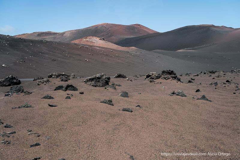 el mar de la tranquilidad es un campo de lava de color rojizo con algunas rocas negras y al fondo más volcanes rojizos