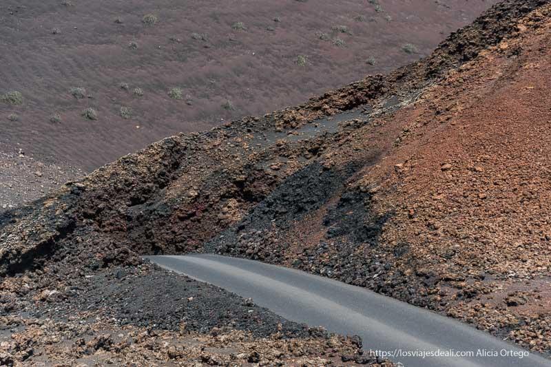 carretera entre laderas de lavas de colores rojos, amarillos y negros