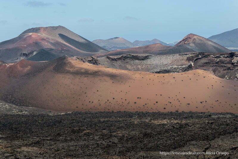 gran cráter con paredes de color arena y otros volcanes detrás en el parque nacional de timanfaya