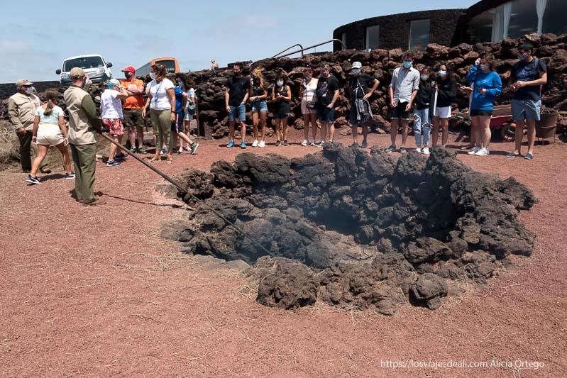 turistas alrededor de un agujero protegido con rocas de lava en el islote de hilario