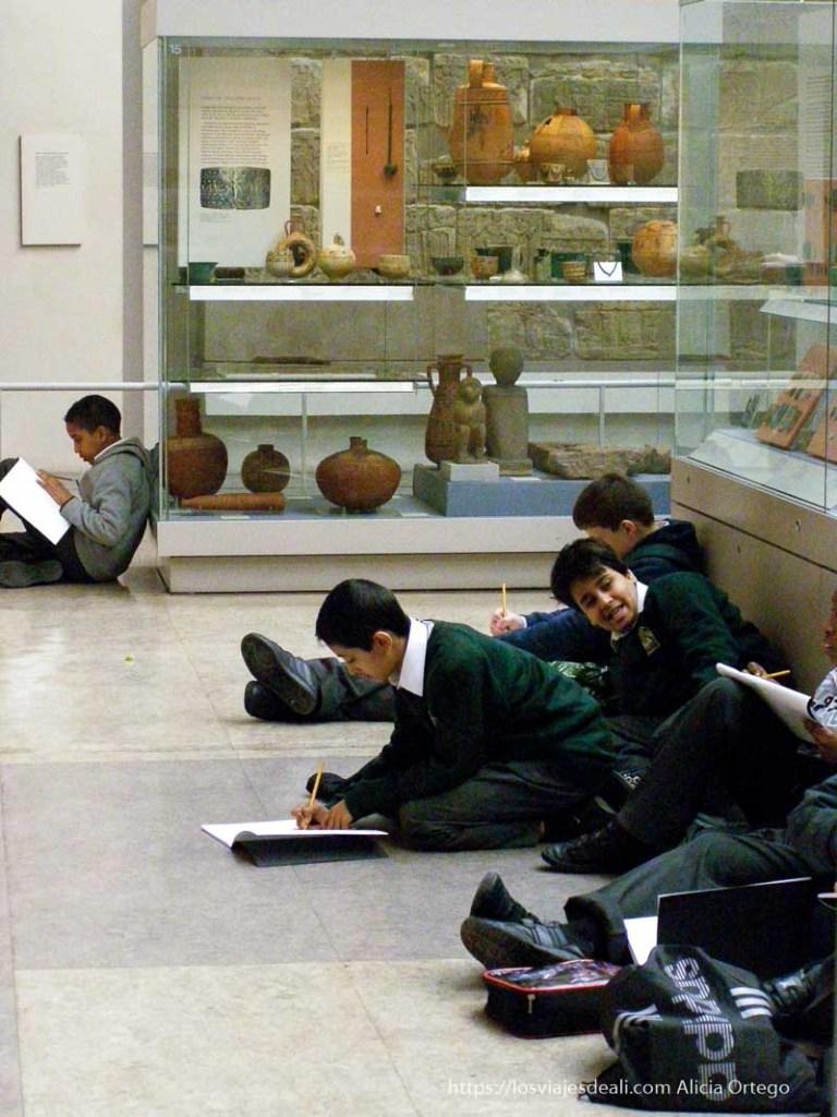 museos arqueológicos del mundo: escolares sentados en el suelo de una sala del antiguo egipto dibujando piezas expuestas