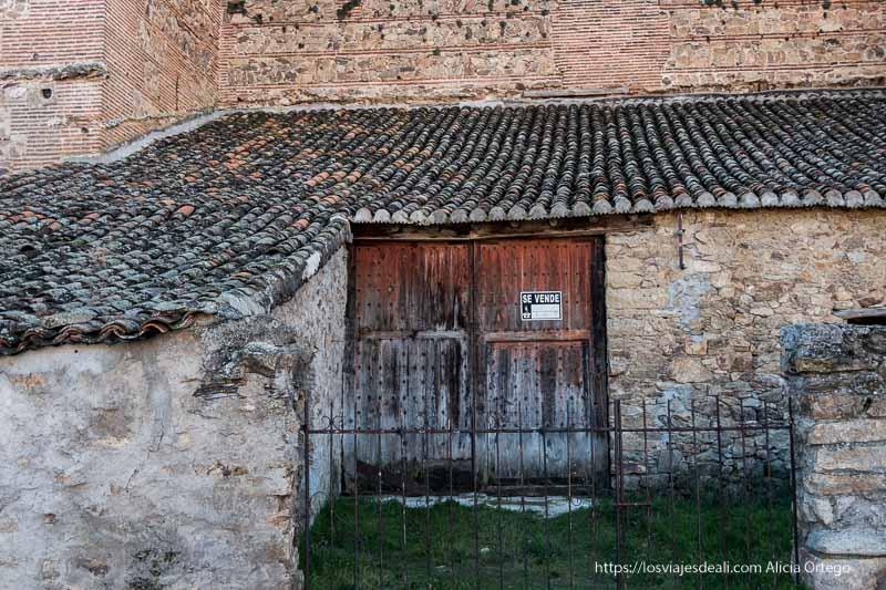 pequeño edificio de piedra con tejado de tejas y puerta de madera con cartel de Se Vende adosado a las murallas de Buitrago del Lozoya