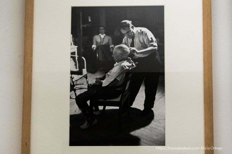 fotografía de picasso sentado mientras el barbero le corta el pelo