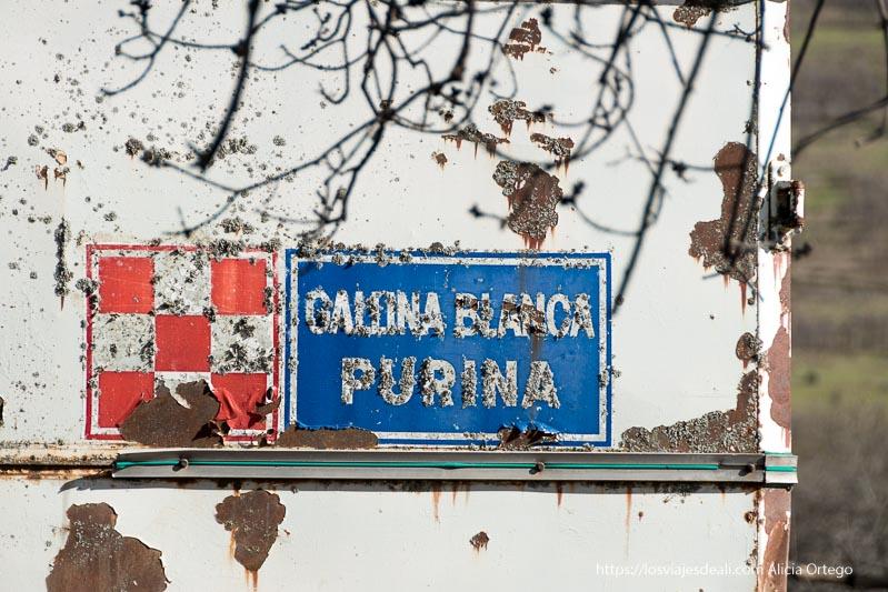 """cartel viejo con desconchones que dice """"Gallina blanca purina"""""""