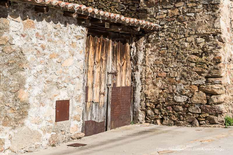 puerta de madera antigua en muro de piedra en el pueblo de canencia