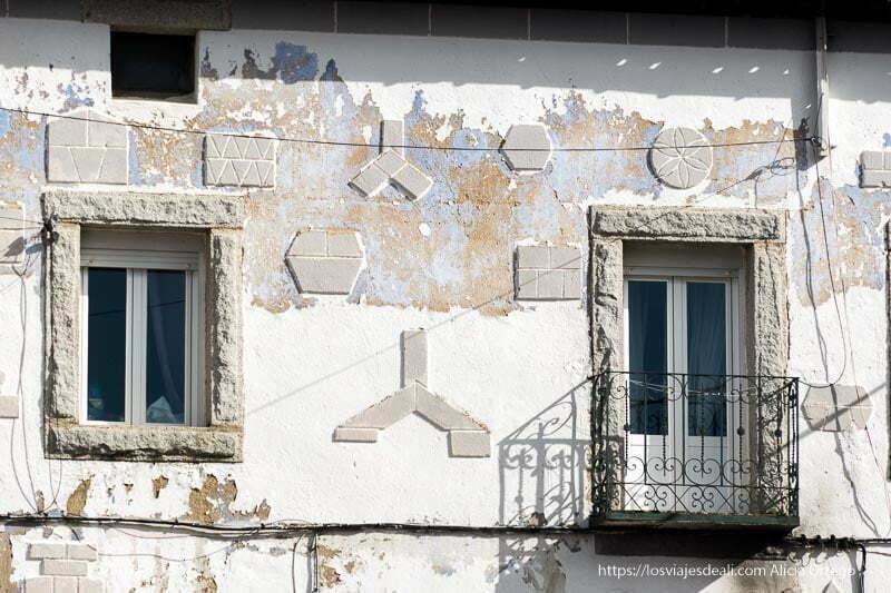 detalle de fachada con ventana y balcón con dinteles de piedra y decoración de figuras geométricas en la fachada