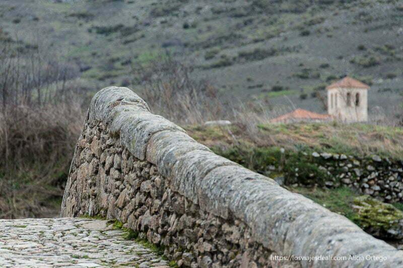 vista del murete del puente medieval y torre de iglesia al fondo