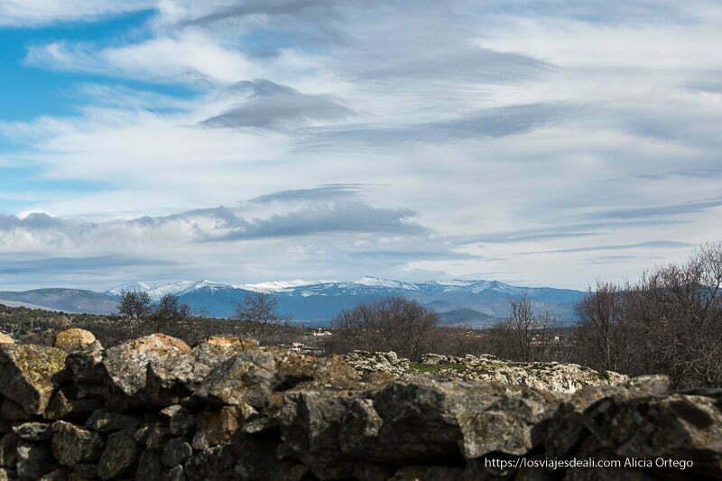 paisaje de montañas con nieve y grandes nubes blancas y grises en canencia
