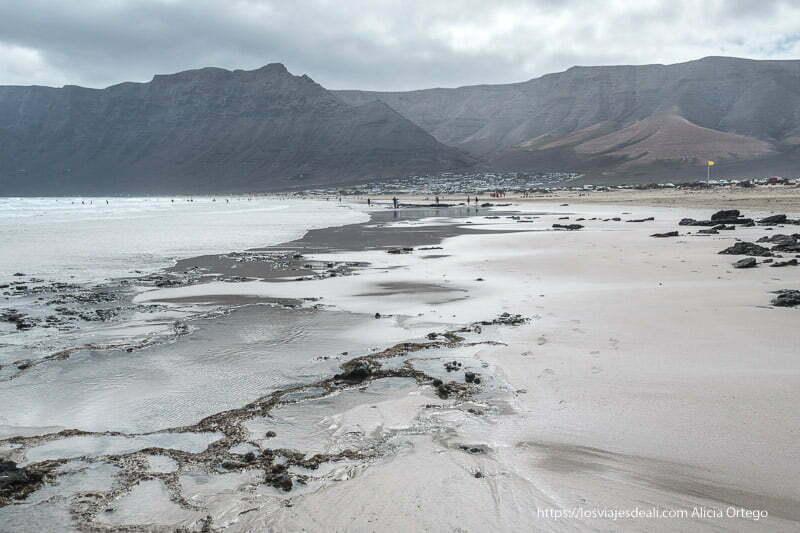ricos de la caleta de famara al fondo con la playa en primer plano en un día muy nublado