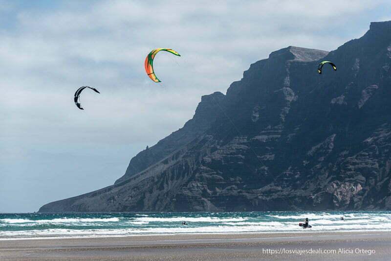 3 velas de kitesurf volando y riscos recortándose en el cielo y el mar