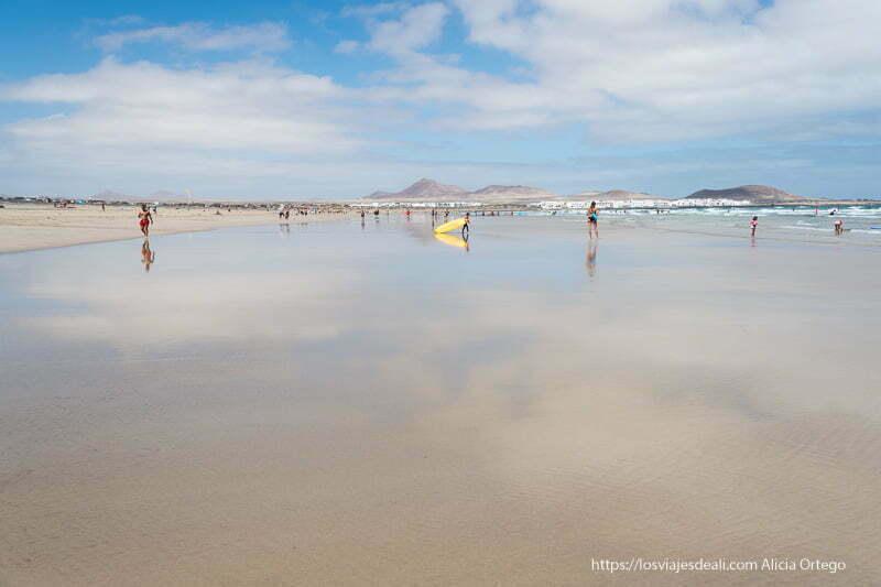 caleta de famara con cielo reflejándose en arena mojada en marea baja
