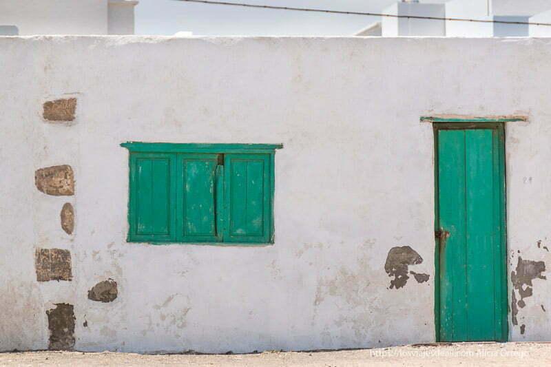 casa de famara con ventana y puerta de madera pintadas de verde casi azul