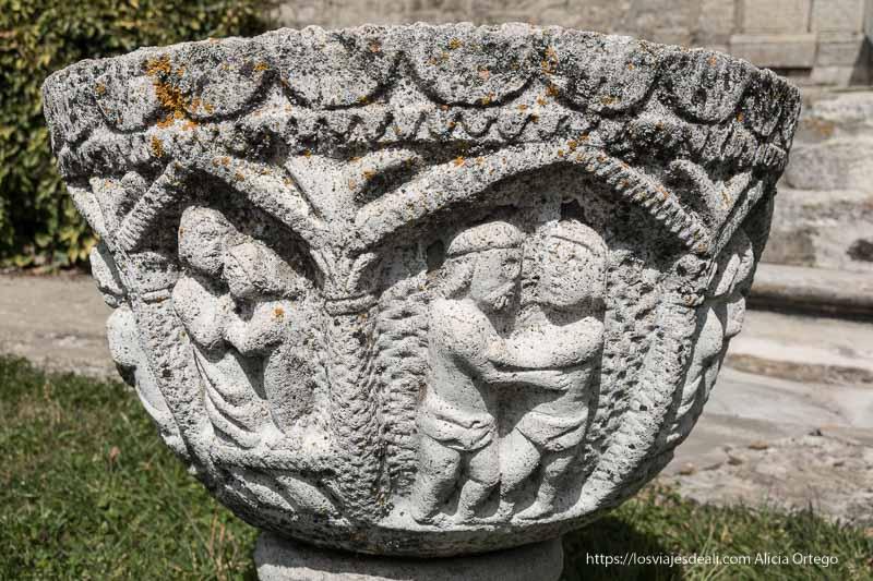 pila bautismal de piedra con figuras de parejas besándose frente a la iglesia de somosierra