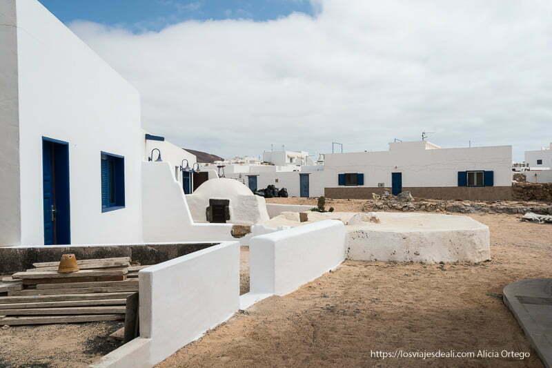 calle de caleta del sebo con suelo de arena y casas blancas con puertas y ventanas azules