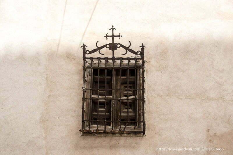 ventana antigua con reja terminada en cruz en parte superior