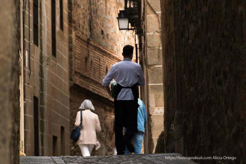 camarero llevando algo en una calle estrecha de Cáceres