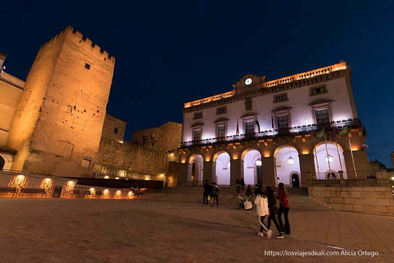 ayuntamiento y torre almenada en la plaza mayor de cáceres en la hora azul iluminados