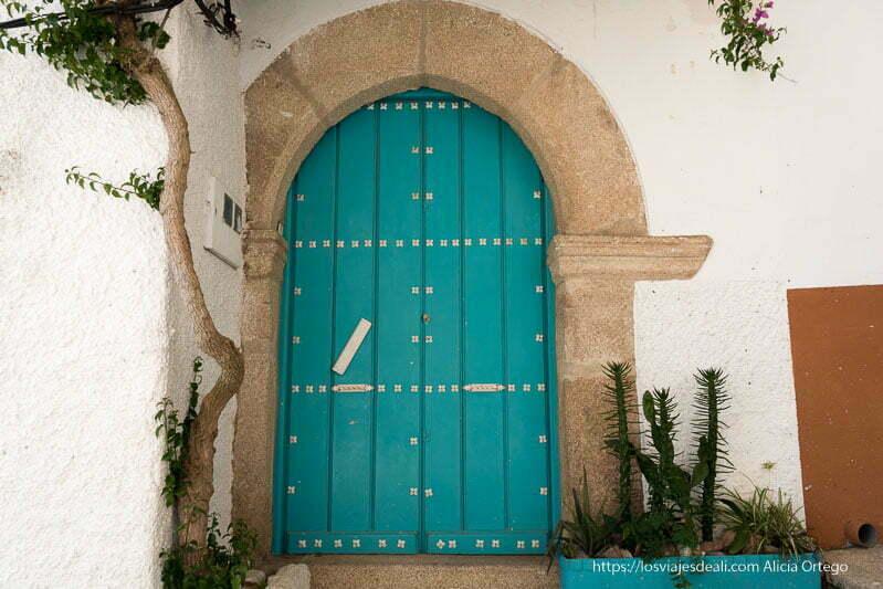 puerta de estilo árabe terminada en arco y pintada de azul turquesa con remaches de metal