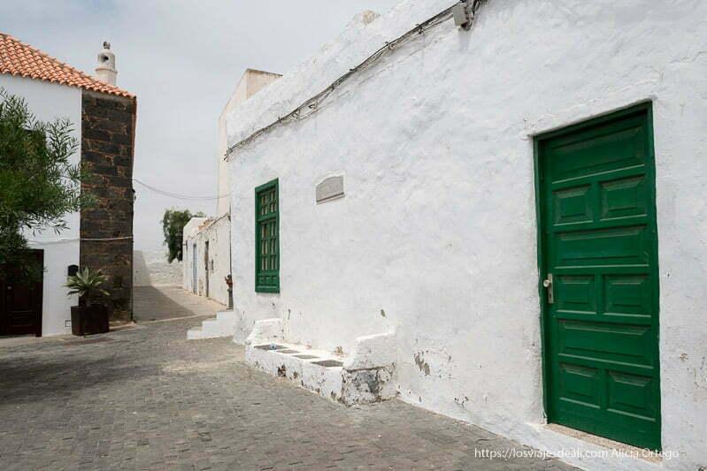 calle de teguise con puerta verde y banco de obra encalado como la pared de la casa