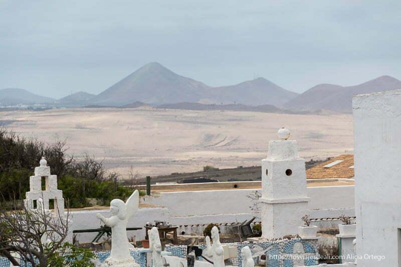paisaje de volcanes en el horizonte y tapias y chimeneas blancas de teguise en primer plano