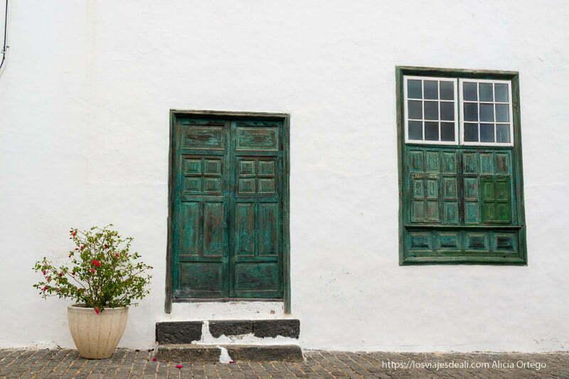 puerta pintada de verde y ventana igual al lado con la parte superior con cristales divididos en cuarterones