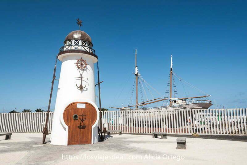 faro conmemorativo y barco pesquero detrás