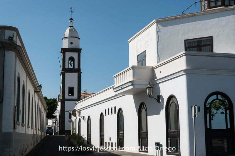 calle con casas blancas y el campanario de san ginés blanco y con piedra negra volcánica