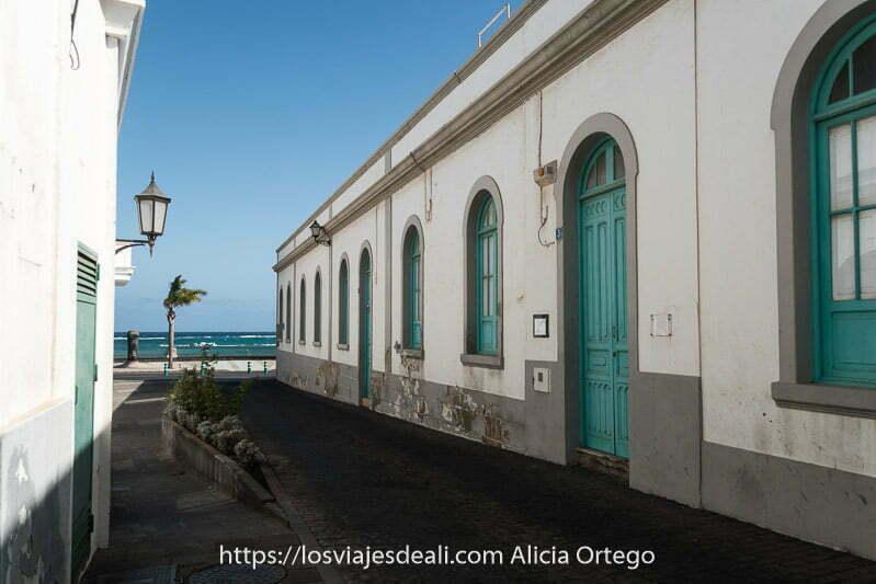 calle que da al mar con edificio con puertas y ventanas verdes terminadas en arcos
