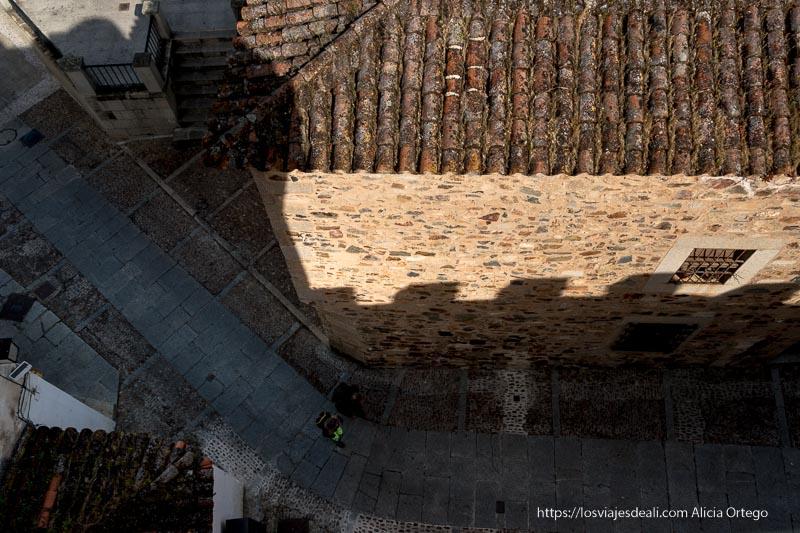 vista desde lo alto de la muralla mirando hacia abajo de una calle con edificio de piedra