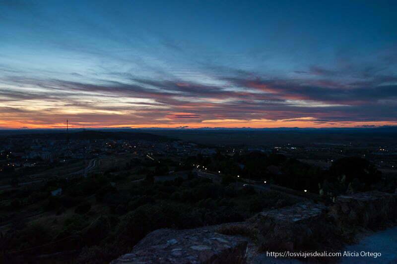 vistas de cáceres anocheciendo con nubes rosas y rojas en el cielo