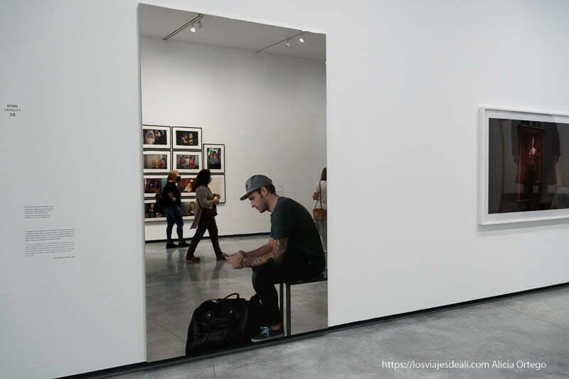 gran espejo con fotografía de un joven sentado mirando el móvil en el museo helga