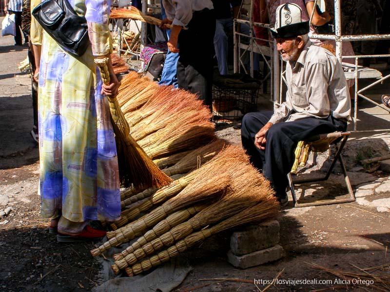 anciano con gorro kirguis de fieltro blanco y negro, vendiendo escobas naturales