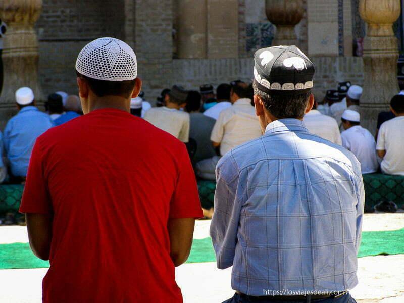 dos hombres con sus gorritos negros y bordados en la hora del rezo en la mezquita de espaldas a la cámara