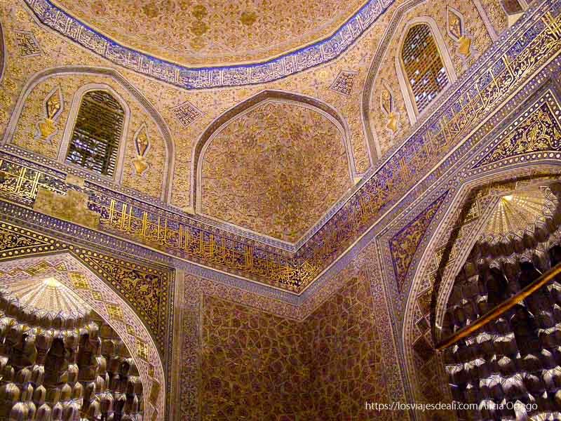 interior de mausoleo con paredes llenas de brocados y aleyas del corán en oro y color azul en la ruta de la seda