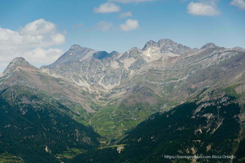 paisaje de montañas con bosques y prados en parte inferior y roca en superior