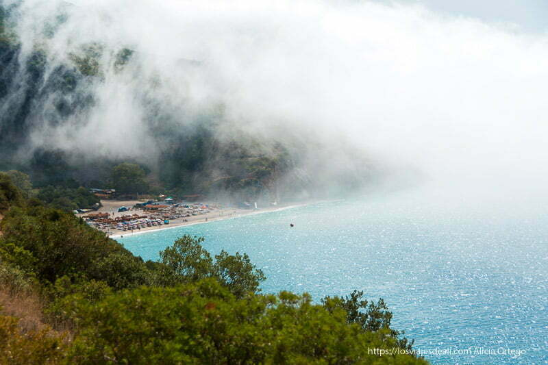 playa escondida entre montañas con neblina sobre ella y mar de colores turquesas en el viaje a Albania