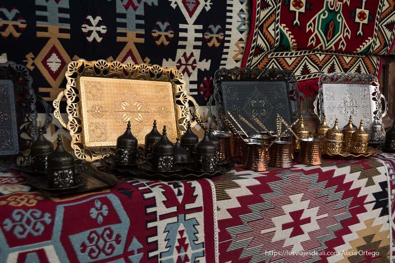 tienda del bazar con alfombras de colores y dibujos geométricos y tacitas de café turco