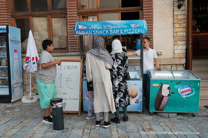 puesto de helado con dos mujeres con velo comprando