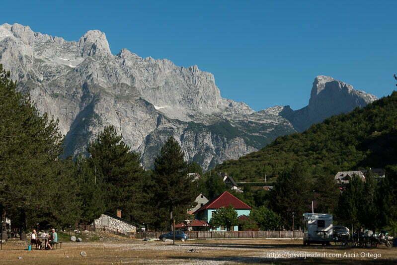 montañas de theth de roca con restos de nieve y casas con tejados muy inclinados entre los árboles
