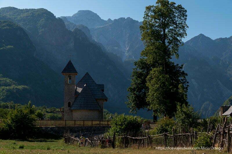 iglesia con campanario y tejados muy inclinados con fondo de montañas y un gran árbol en el viaje a Albania