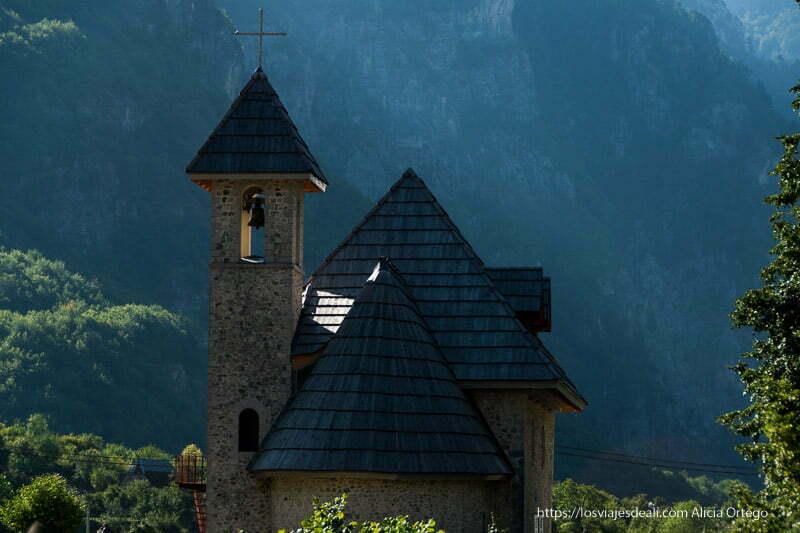 tejado de la iglesia de theth con campanario y cruz y el fondo de montañas