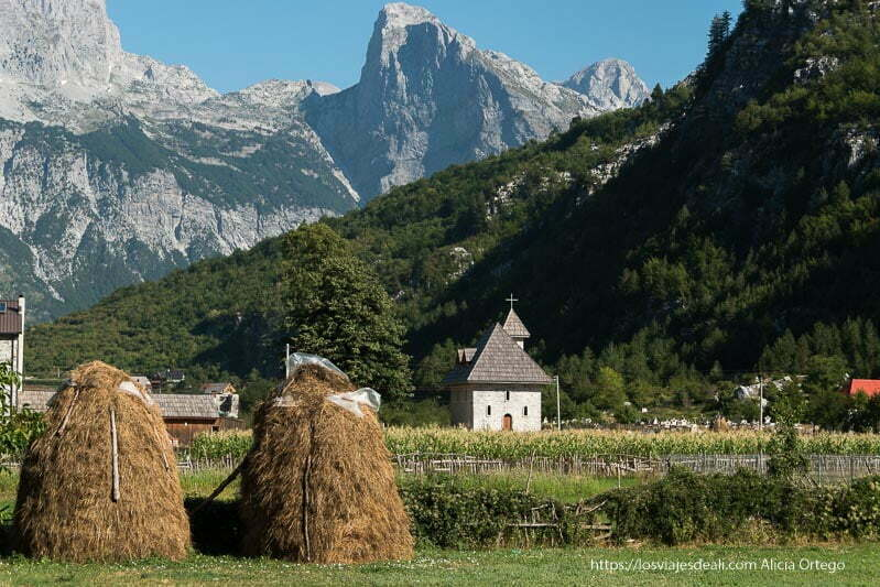 paisaje con la iglesia y montones de paja, un campo de maíz y montañas al fondo