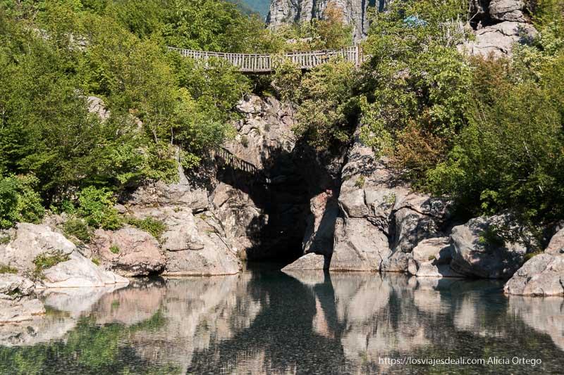 poza de agua transparente y paredes de roca con un puente de madera en la parte superior