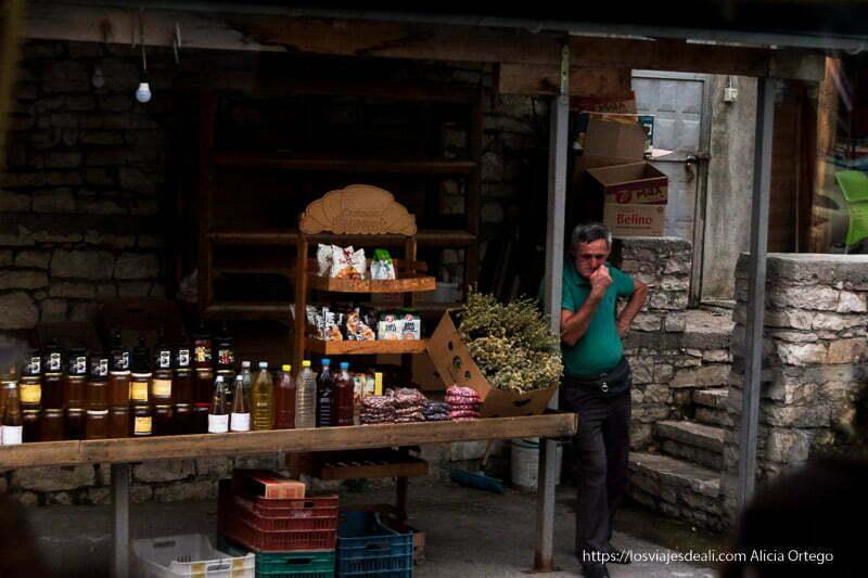 puesto de venta de miel y otros productos con el vendedor apoyado