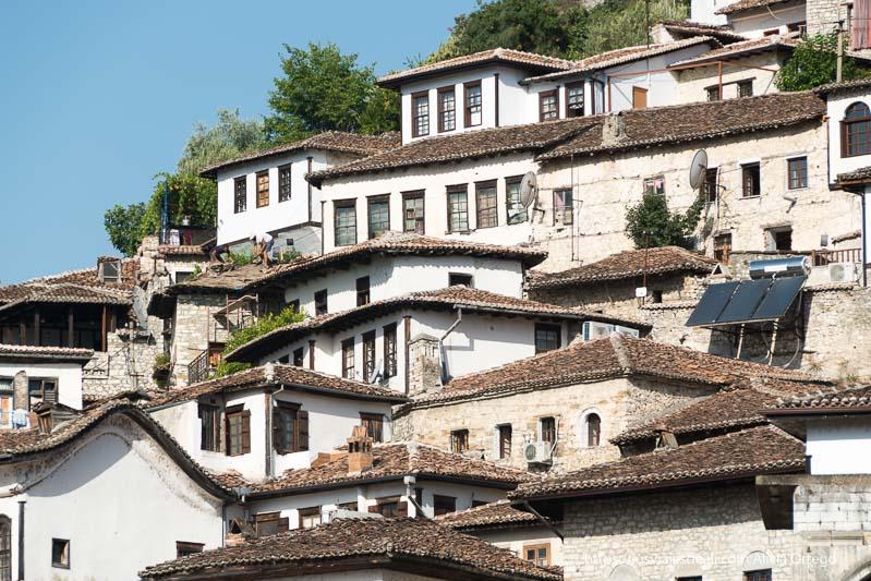 casas blancas con tejados de teja marrón en Berat, escalonadas en la montaña