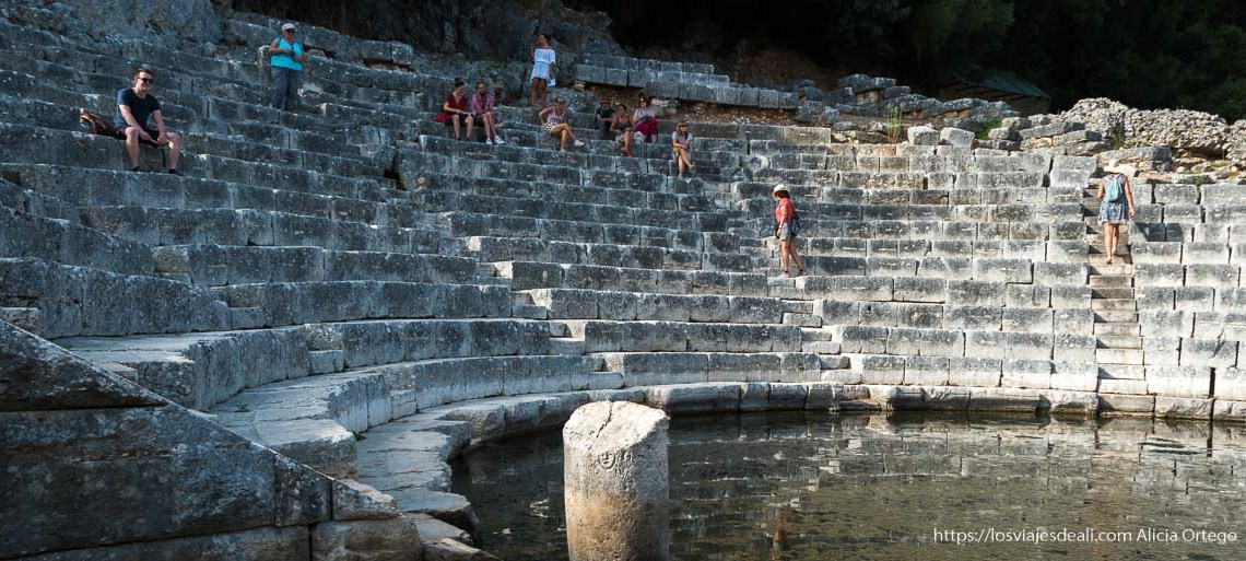 teatro de las ruinas de butrinto con algunos turistas sentados