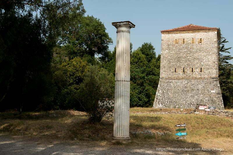 torre de piedra con tejado rojo y columna tipo griega en las ruinas de butrinto