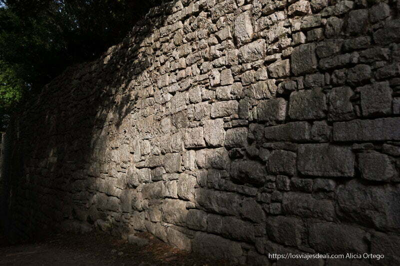 muralla entre sol y sombra con piedras de distintos tamaños