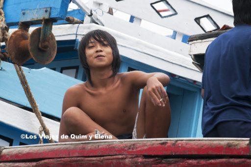 Chico fumando sobre un barco, fotografías